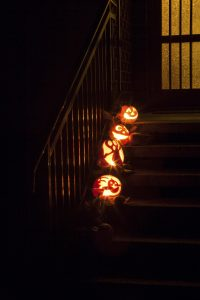 Carved pumpkins line the steps of this spooky front porch.